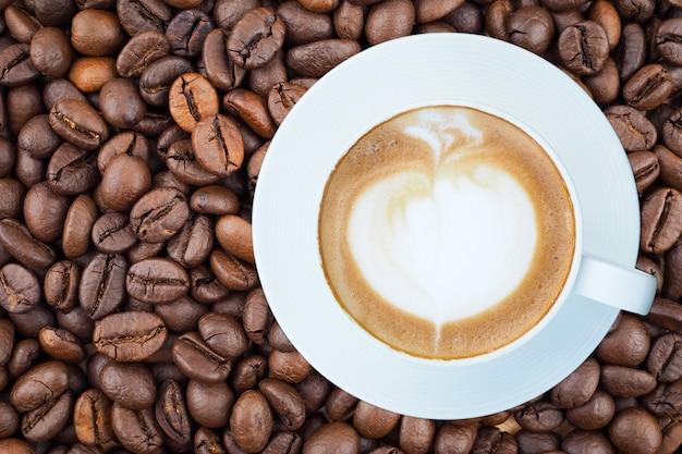 Café au lait chaud dans une tasse blanche sur fond de grains de café
