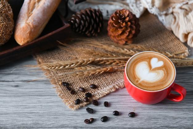 Café au lait de coeur dans une tasse rouge avec du pain.