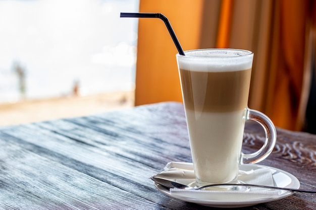 Café au lait dans un verre sur une table en bois, photo horizontale, espace copie