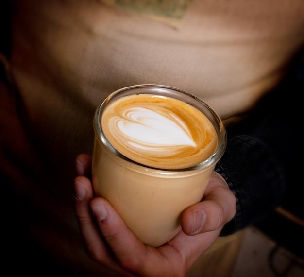 Café au lait avec du lait dans les mains