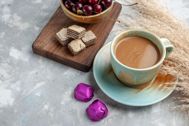Café au lait avec des gaufres et des cerises aigres fraîches sur la lumière