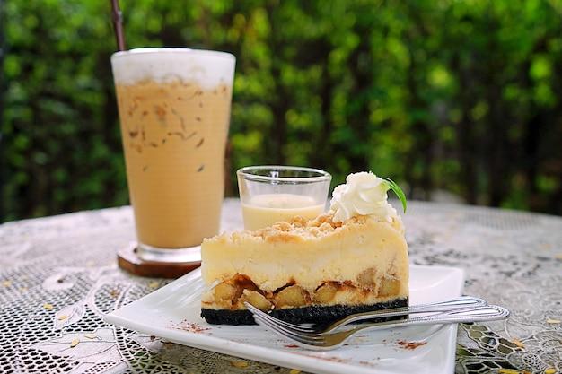 Café au lait glacé avec tarte au caramel sur table blanche avec fond de jardin vert