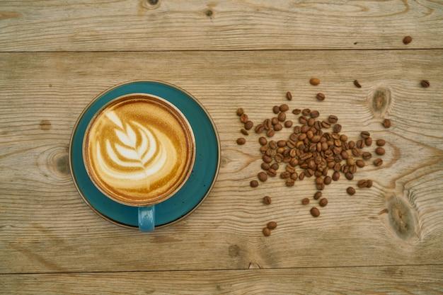 Café au lait et grains de café sur la table en bois
