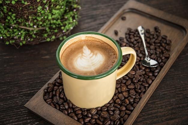 Café au lait avec grains de café, tasse de café avec de beaux arts latte.