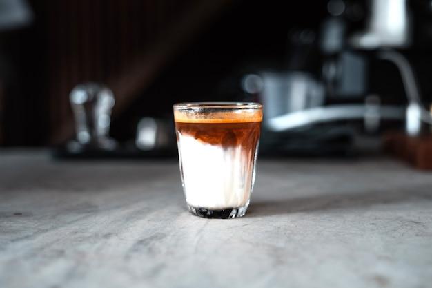 Café au lait, lait et café dans un verre de la machine