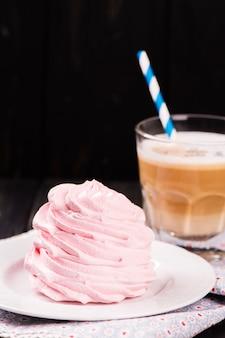 Café au lait avec de la meringue rose croustillante sur un fond en bois noir.