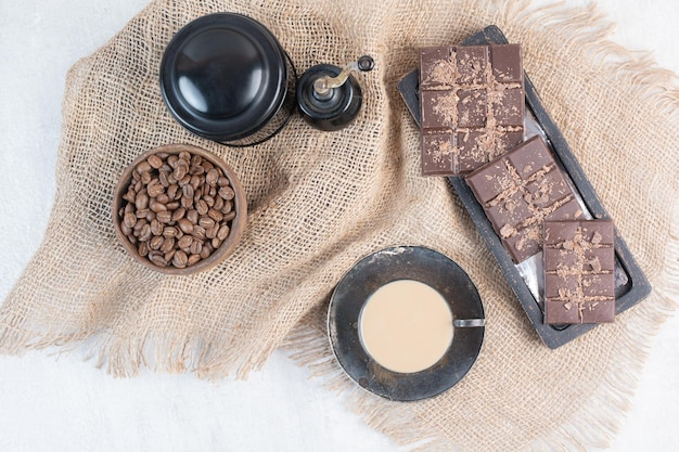 Café, barre de chocolat et grains de café sur toile de jute