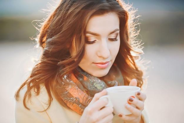 Café. belle fille buvant du thé ou du café. beauté modèle femme dans un long manteau jaune et une écharpe à la mode. couleurs chaudes toniques