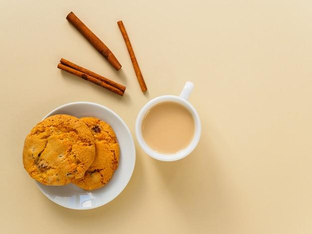 Café, biscuits et cannelle sur fond jaune.