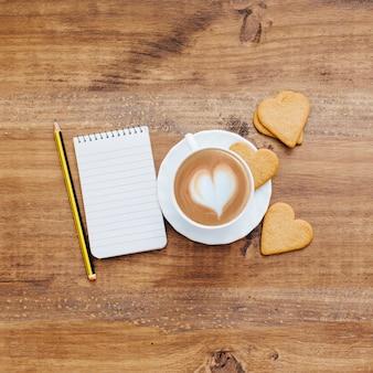 Café avec des biscuits de coeur et cahier