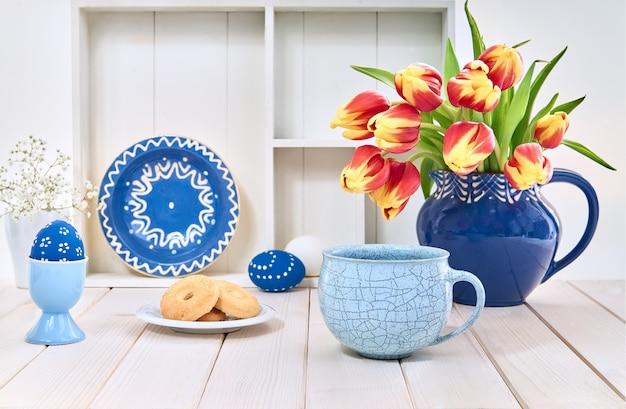 Café et biscuits sur une table blanche avec des tulipes rouges et des décorations de printemps