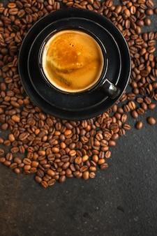 Café boire dans une tasse blanche et saupoudrer de grains de café sur la table