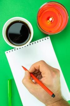 Café, bougie, bloc-notes et main masculine forte avec un feutre sur fond de noël. décoration du nouvel an.