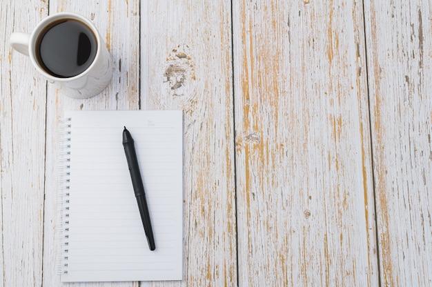 Café et un cahier sur fond de bois clair