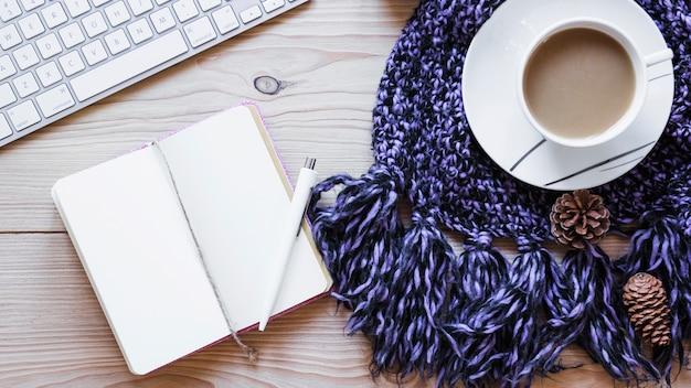 Café et cahier près de l'écharpe et du clavier