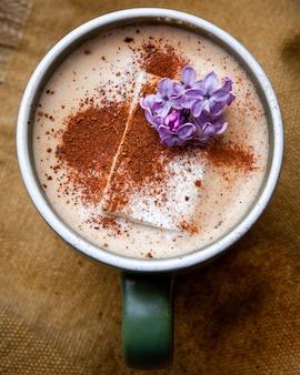 Café cappuccino chaud avec des pétales de fleurs dans une tasse sur un morceau de sac