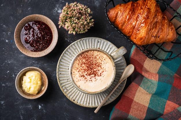 Café cappuccino avec croissant sur la table