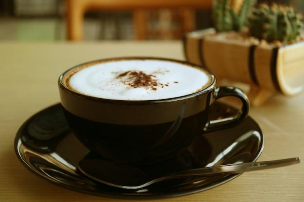 Café cappuccino dans une tasse noire servi sur table en bois