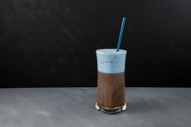 Café cappuccino ou latte avec mousse de lait bleue dans un grand verre.