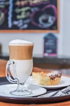 Café cappuccino et un morceau de gâteau sur un plateau de service de restaurant.