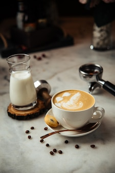 Café cappuccino pour le petit déjeuner avec du lait et des biscuits sur une table en marbre blanc