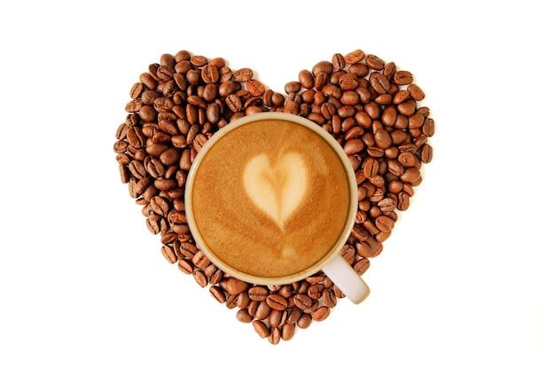 Un café cappuccino sur tas de grains de café torréfiés en forme de coeur