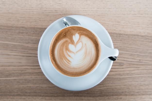 Café cappuchino dans une tasse en porcellan blanc et une cuillère en argent.