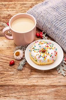 Café chaud avec un beignet. boisson d'automne pour la bonne humeur avec plaid, cynorhodons frais, feuilles et fleurs.