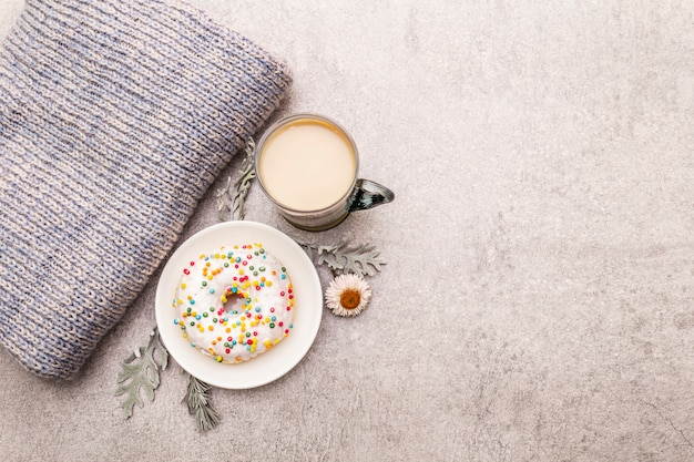 Café chaud avec un beignet. boisson d'hiver pour la bonne humeur avec pull, feuilles et fleurs.