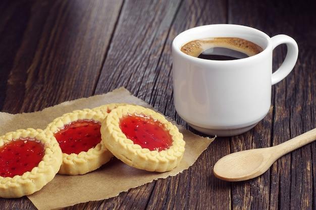 Café chaud et biscuits avec de la confiture sur une table en bois foncé