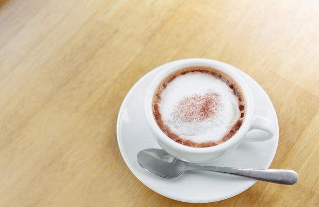 Café chaud dans une tasse blanche avec une cuillère en métal sur fond de table en bois
