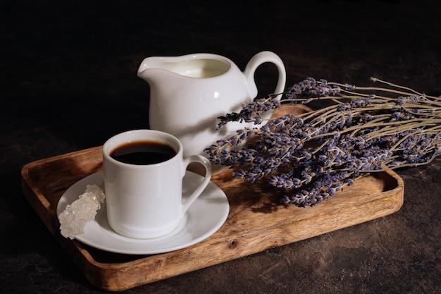 Café chaud dans une tasse blanche de lait et de lavande sur un plateau en bois