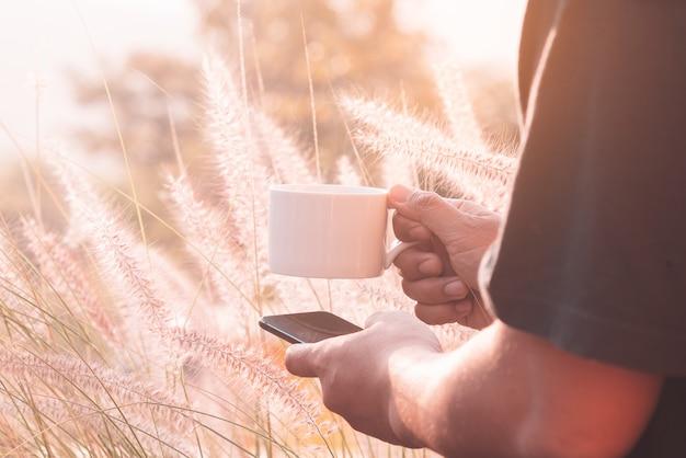 Café chaud dans une tasse blanche et un smartphone tenait par personne