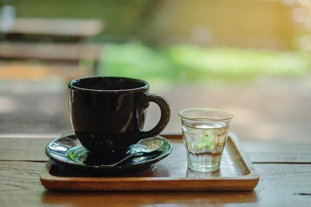 Café chaud dans une tasse noire avec un petit verre d'eau placé sur un plateau en bois dans un café