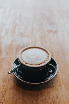 Café chaud dans une tasse noire sur une table en bois.