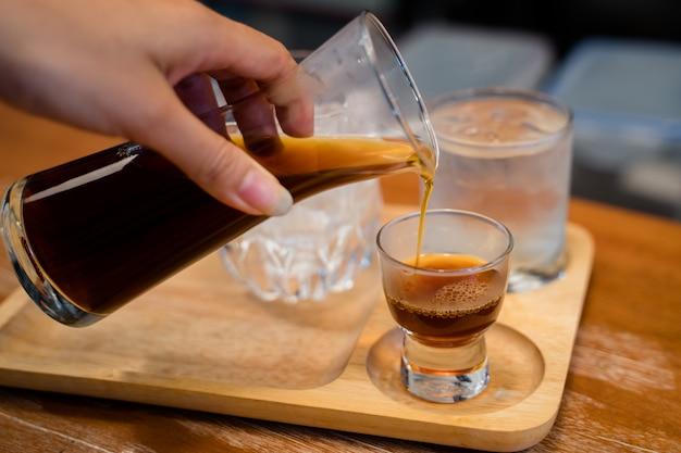 Café chaud dégoulinant servi avec un verre de glace