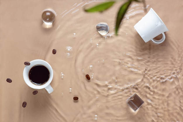 Café chaud éclaboussant dans la tasse, l'eau et les haricots