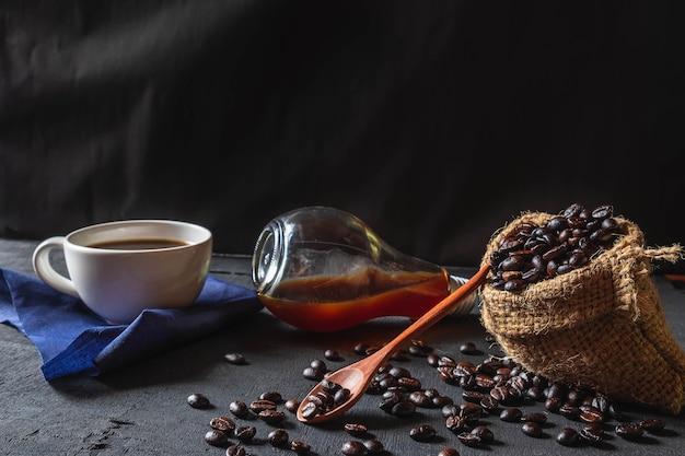 Café chaud et grains de café crus sur fond noir.