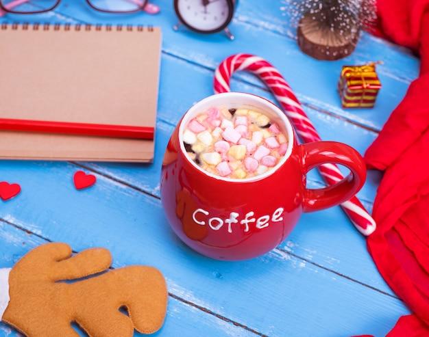 Café chaud à la guimauve dans une tasse en céramique rouge