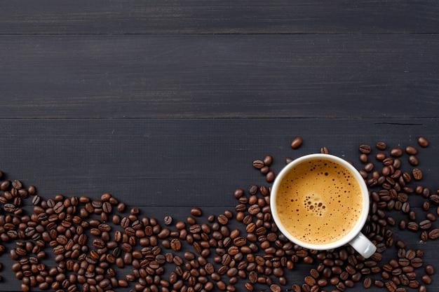 Café chaud et haricots sur fond en bois. vue de dessus