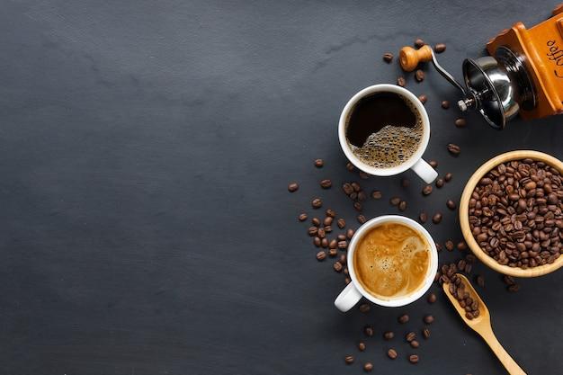 Café chaud, haricots et moulin à main sur fond de tableau noir. espace pour le texte. vue de dessus