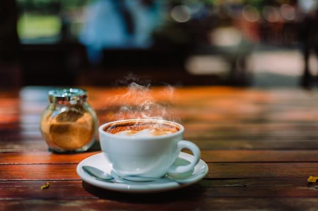 Café chaud latte mousse cappuccino en spirale sur une table en bois dans un café