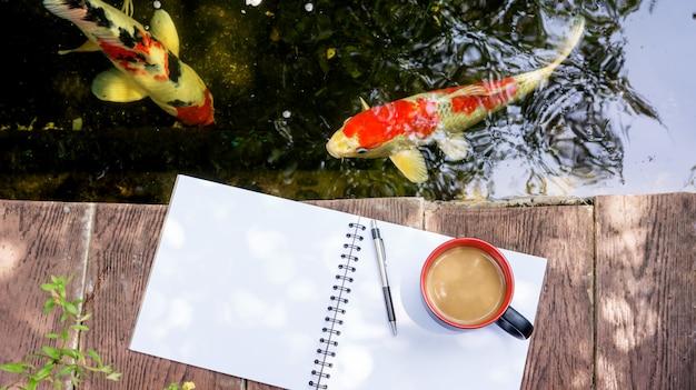Café chaud, livre et stylo près d'un étang de carpes de fantaisie.