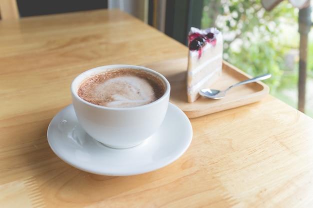 Café chaud moka avec gâteau au lait et aux myrtilles dans un café de campagne