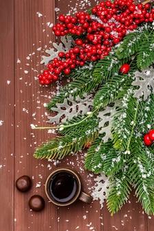 Café chaud de noël. sapin du nouvel an, rose des chiens, feuilles fraîches, bonbons au chocolat et neige artificielle.