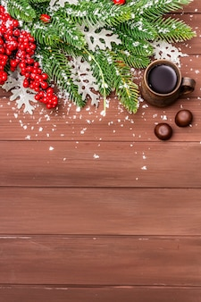 Café chaud de noël, sapin, feuilles fraîches, bonbons au chocolat et neige artificielle.