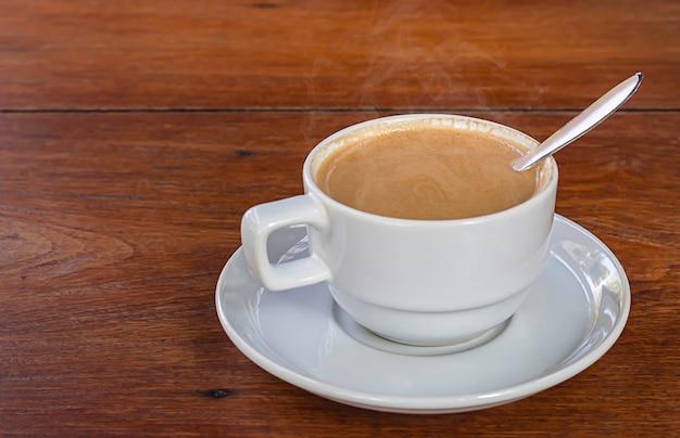 Café chaud en verre blanc sur une table en bois
