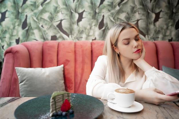 Cafe city lifestyle femme sur téléphone, boire du café texto sms sur smartphone dans un café urbain branché.