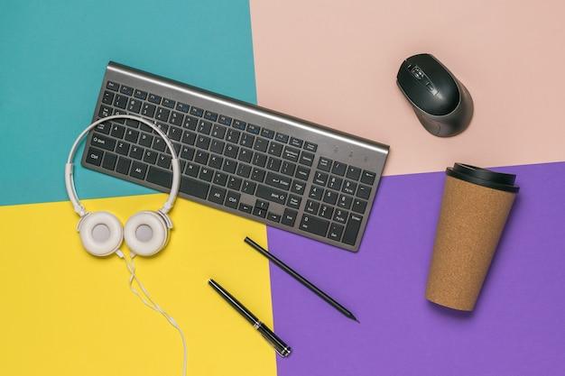 Café, clavier, souris, écouteurs et crayons