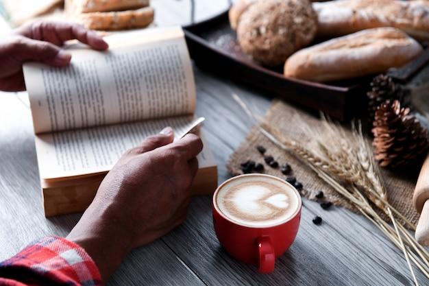 Café de coeur dans une tasse rouge avec des gens qui lisent un livre.